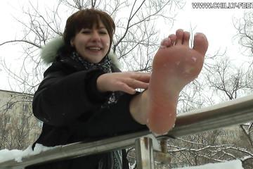 Девушка зимой по улице ходит босой