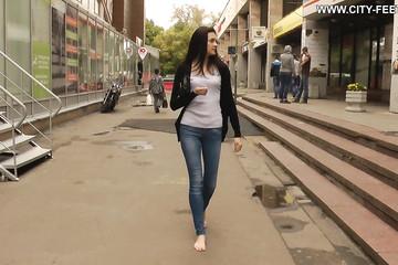 Девушка в джинсах ходит босой по городу